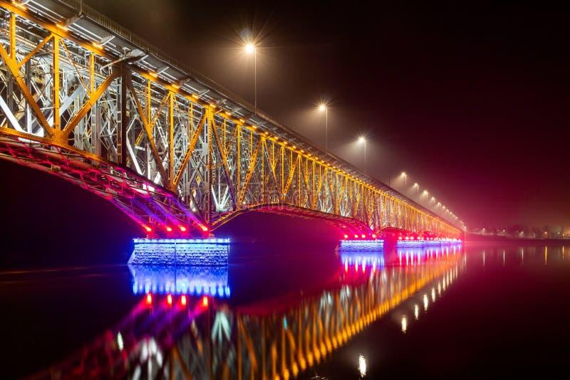 Plock, Polen - Straßenbahnbrücke über die Weichsel Wisla in nachts beleuchtet stockbilder