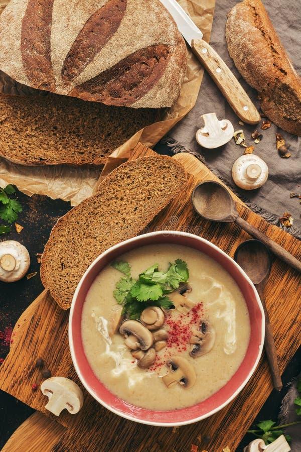Plocka svamp kräm- soppa med hemlagat rågbröd på en skärbräda Vintervärmesoppa Bästa sikt, lekmanna- lägenhet arkivbild