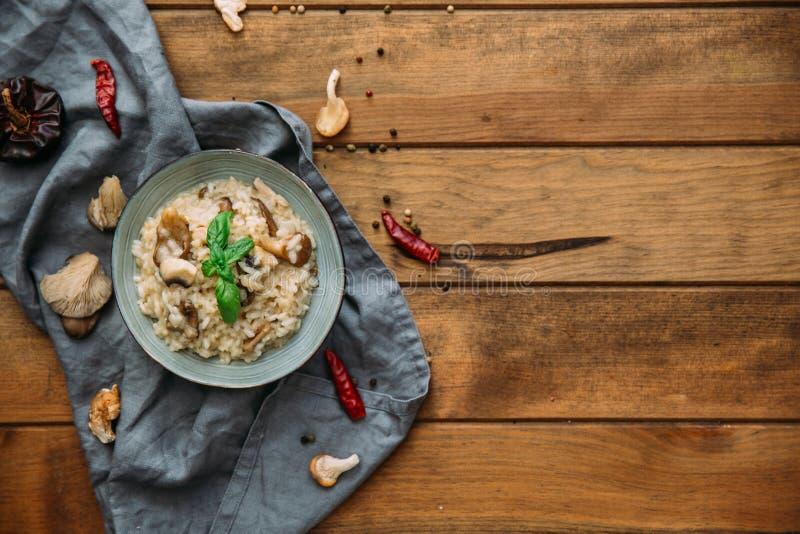 Plocka svamp risotto, skott från ovannämnt på mörka lantliga texturer fotografering för bildbyråer