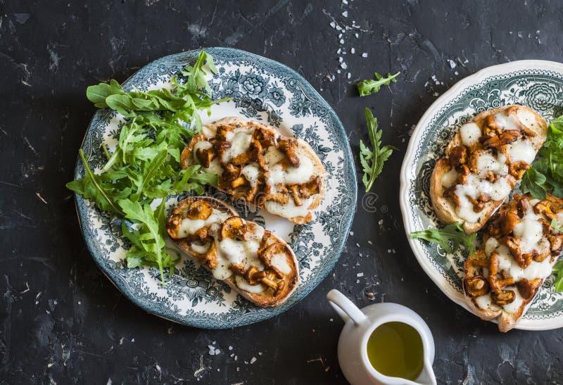 Plocka svamp tartine Bakade smörgåsar med den champinjonkantareller och mozzarellaen på en mörk bakgrund arkivfoto