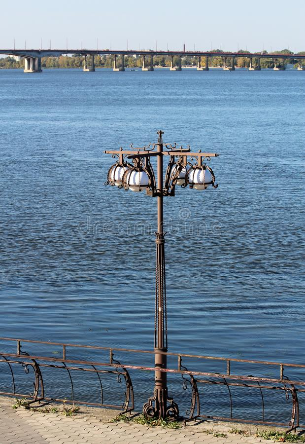 plofony bianco nella scultura del metallo con un palo della luce con un fondo del fiume e del ponte blu fotografie stock