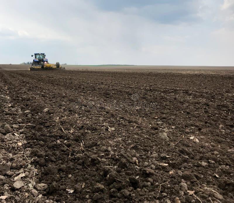 Plogat fält för potatis i brun jord på den öppna bygdnaturen royaltyfri foto