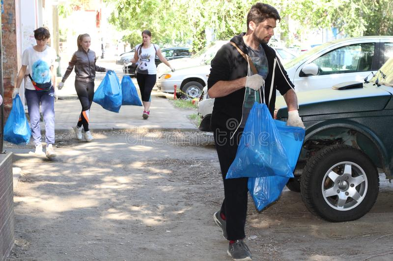 Plogging. girls run and collect garbage in bags on the streets Saratov, Russia, 10 June 2018 royalty free stock photography