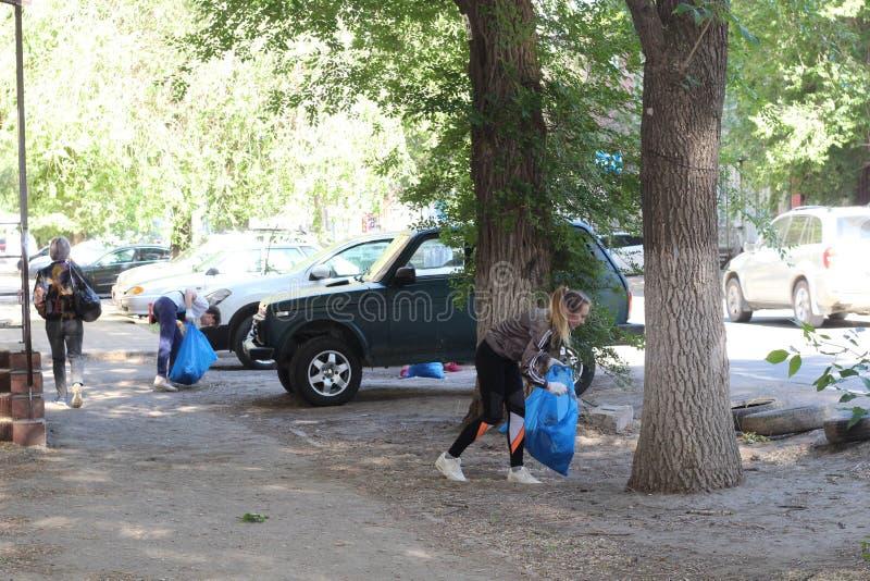 Plogging junge Leute lassen laufen und sammeln Abfall in den Taschen auf den Stra?en von Saratow, Russland, am 10. Juni 2018 lizenzfreie stockfotografie