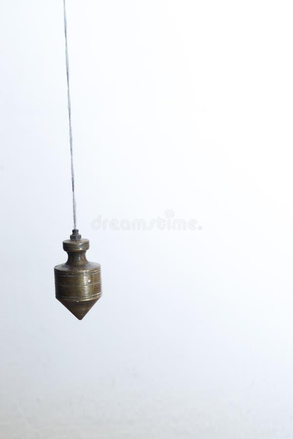 Plomada del metal colgada en una cuerda imágenes de archivo libres de regalías