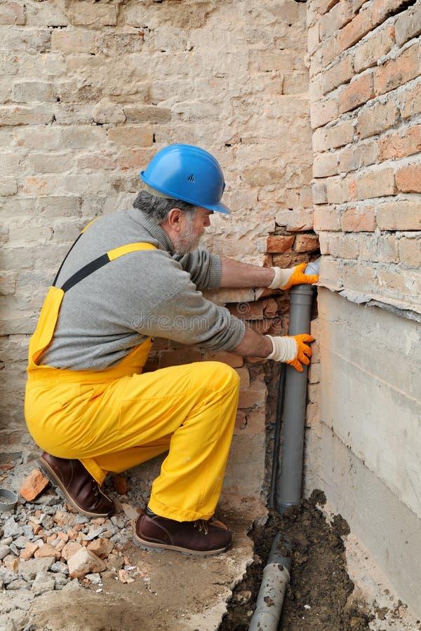 Plombier au chantier de construction installant le tube de système d'égouts image libre de droits