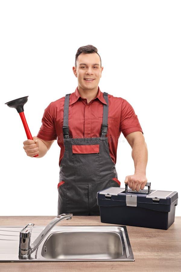 Plombier avec le plongeur et la boîte à outils se tenant derrière l'évier photo stock