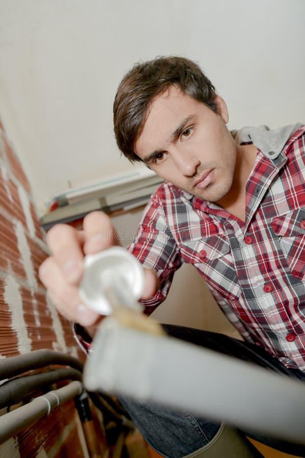 Plombier collant un tuyau photographie stock