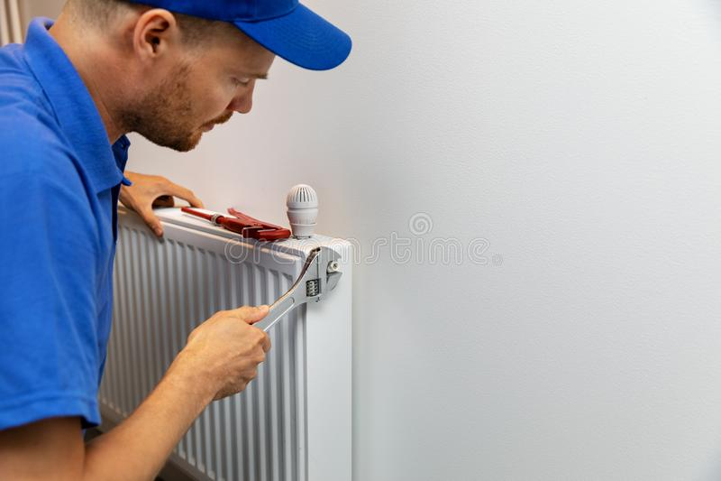 Plombier d'installation de système de chauffage de Chambre installant le radiateur photographie stock libre de droits