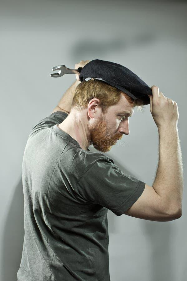 Plombier dans le chapeau avec la barbe rouge photographie stock