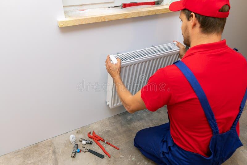 Plombier installant le radiateur de chauffage sur le mur photos stock