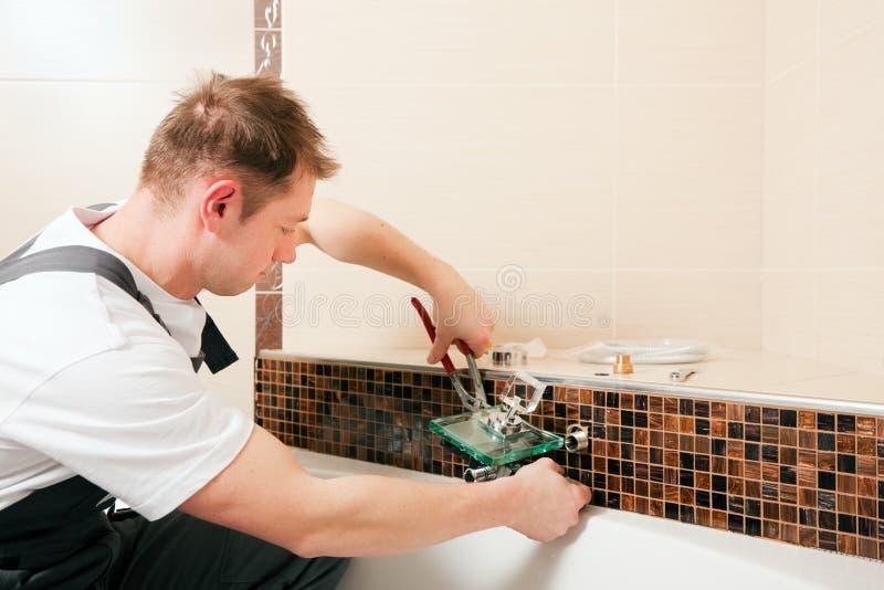 Plombier installant une prise de mélangeur dans une salle de bains photos stock