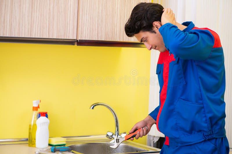 Plombier réparant le robinet à la cuisine photographie stock libre de droits