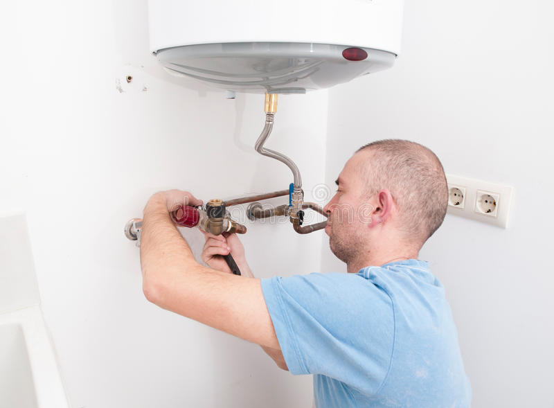 Plombier réparant une chaudière électrique photos stock