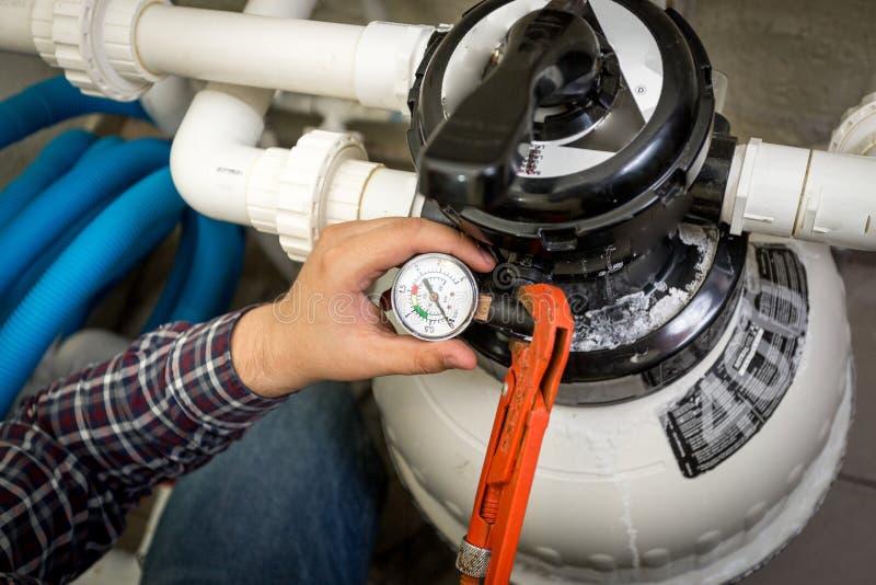 Plombier vérifiant le manomètre sur la grande pompe hydraulique image stock