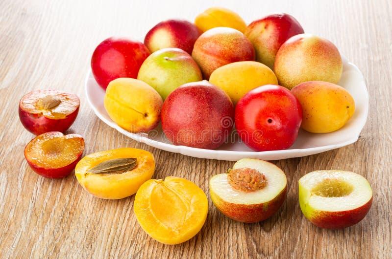 Plommoner aprikors, nektariner i maträtt, halvor av frukter på trätabellen royaltyfri foto