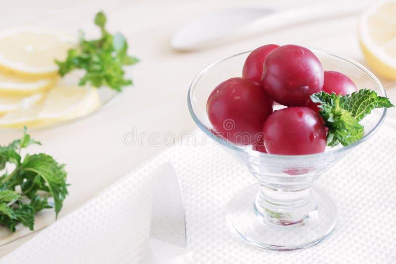 Plommoner ligger i en exponeringsglaskrämbunke på tabellen, citronsnitt in i skivor, sidor för den nya mintkaramellen, sunda food royaltyfri foto