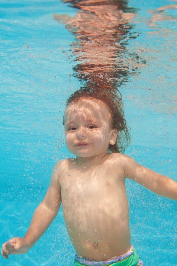 Plongée heureuse de gosse d'enfant en bas âge sous l'eau images libres de droits