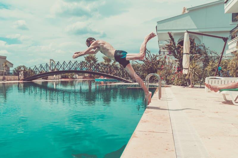 Plongée sexy de jeune homme dans la piscine dans une station de vacances photo stock