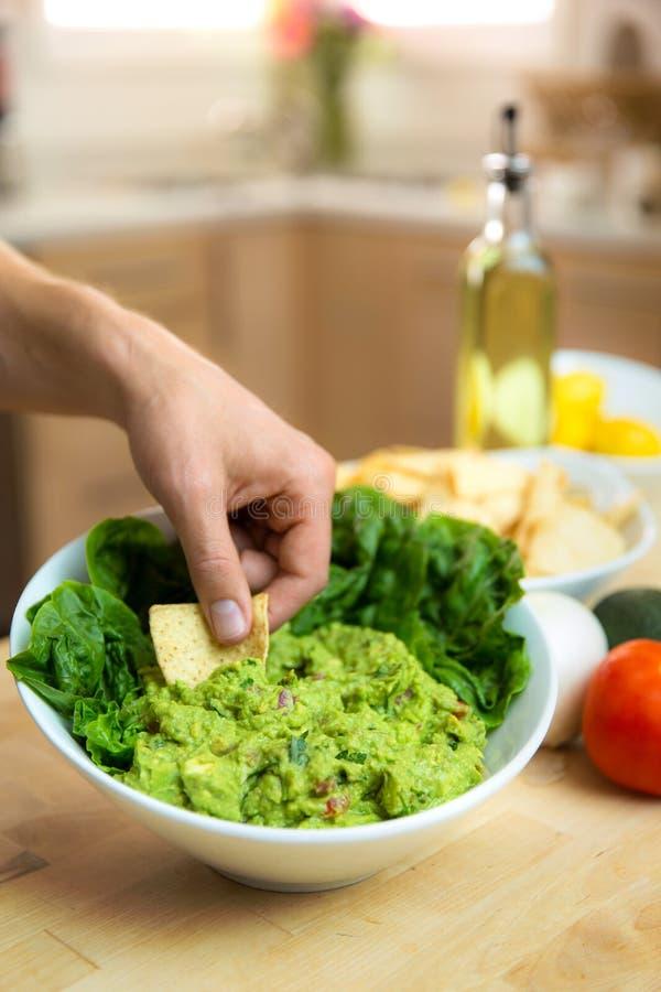 Plongeant la puce dans un bol délicieux frais de guacamole organique fait main à la maison dans la cuisine photo stock
