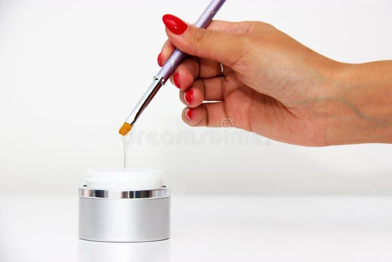 Plongement de la brosse dans des vernis à ongles images stock
