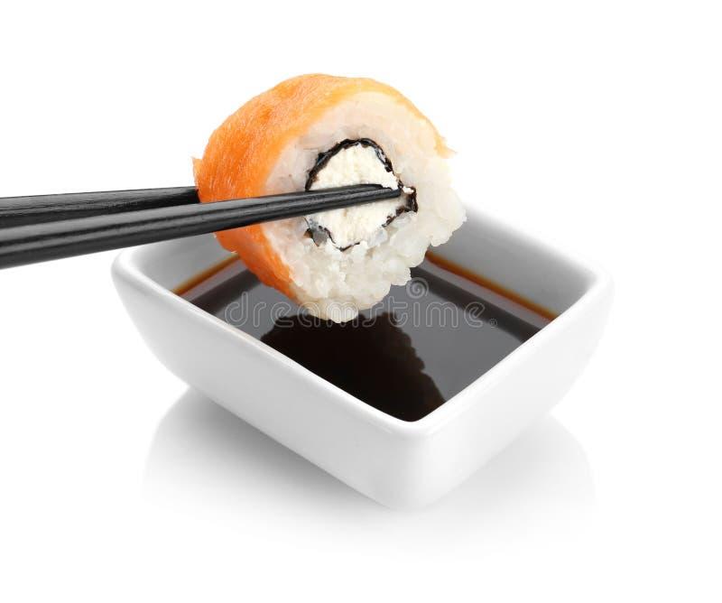 Plongement du petit pain savoureux dans la cuvette avec la sauce de soja photographie stock libre de droits