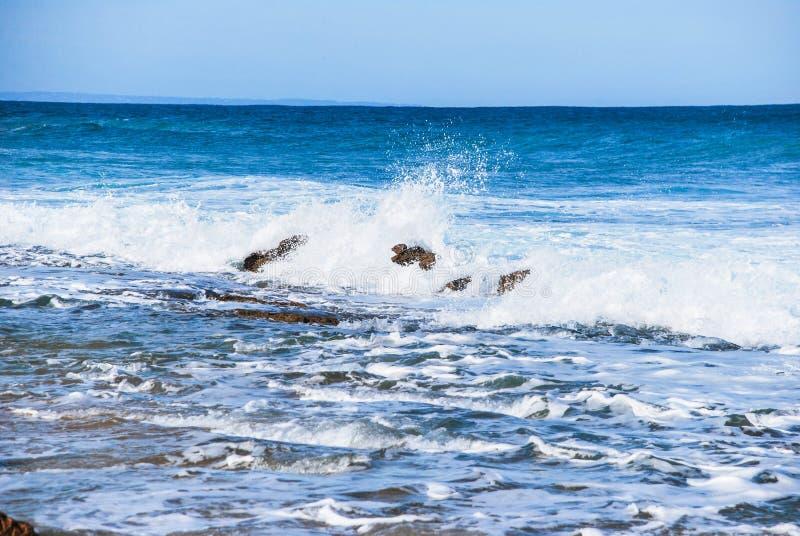 Plongement léger d'océan et vagues s'effondrantes, se cassant sur la couleur bleue naturelle d'océan de roches, l'eau mousseuse photos stock