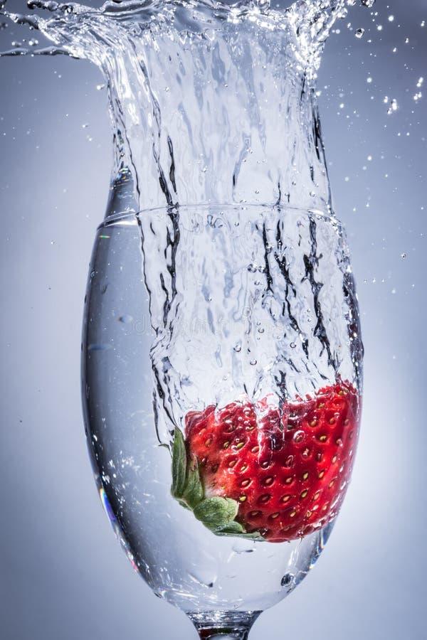 Plongeon d'éclaboussure de fraise dans l'eau dans un verre de vin photo libre de droits
