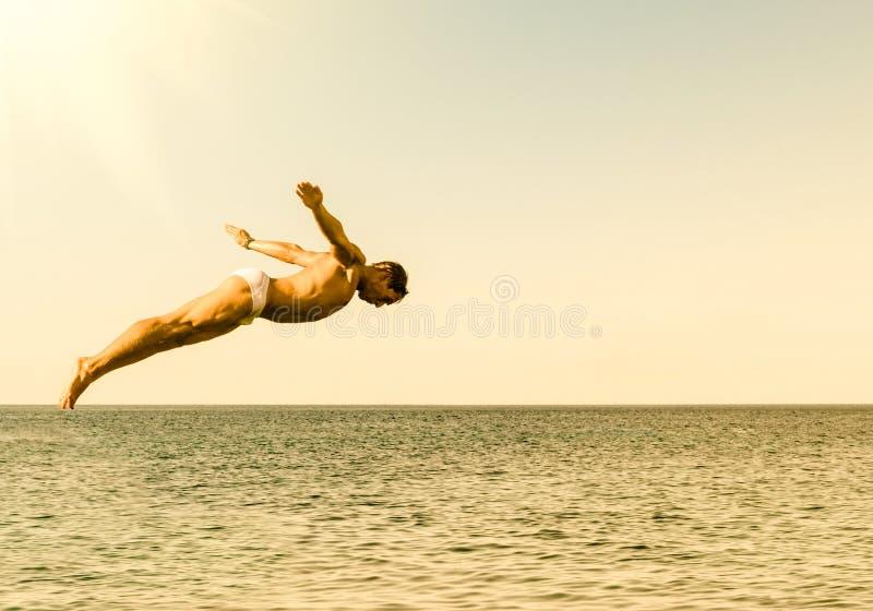 Plongeur de falaise sautant en mer contre le ciel au coucher du soleil photographie stock libre de droits
