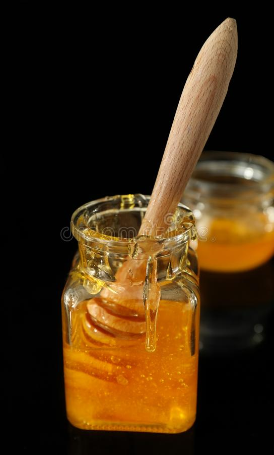 Plongeur en bois dans le pot avec du miel sur le fond foncé photos stock