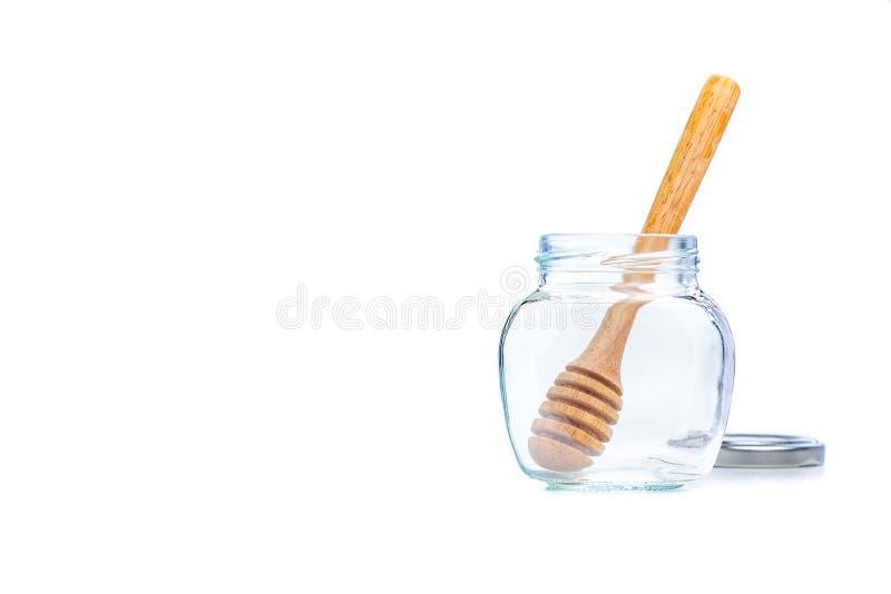 Plongeur en bois de miel dans un pot en verre clair vide sur le fond blanc photo stock