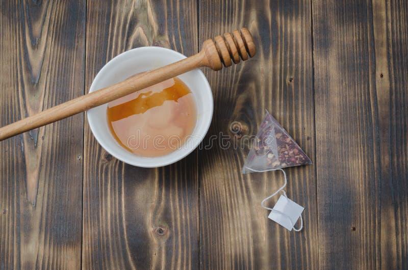 plongeur sur une cuvette blanche avec le sachet à thé de miel et, table en bois Vue sup?rieure photos stock