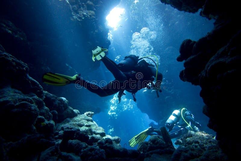 Plongeurs autonomes en caverne sous-marine image stock