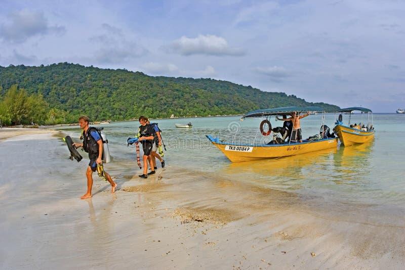 Plongeurs autonomes marchant sur la plage après un voyage de piqué photo libre de droits