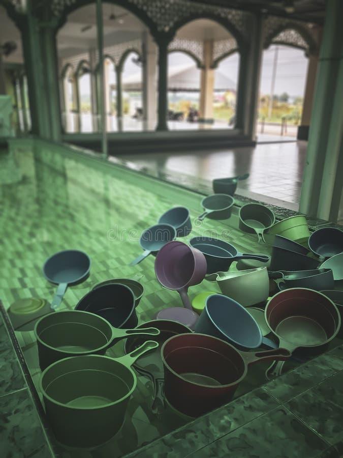 Plongeurs en plastique colorés de l'eau de filtre amorti de cru habituellement employés par des musulmans pour écoper l'eau pour  photographie stock