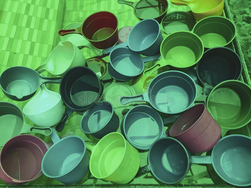 Plongeurs en plastique colorés de l'eau habituellement employés par des musulmans pour écoper l'eau pour la purification d'abluti images libres de droits