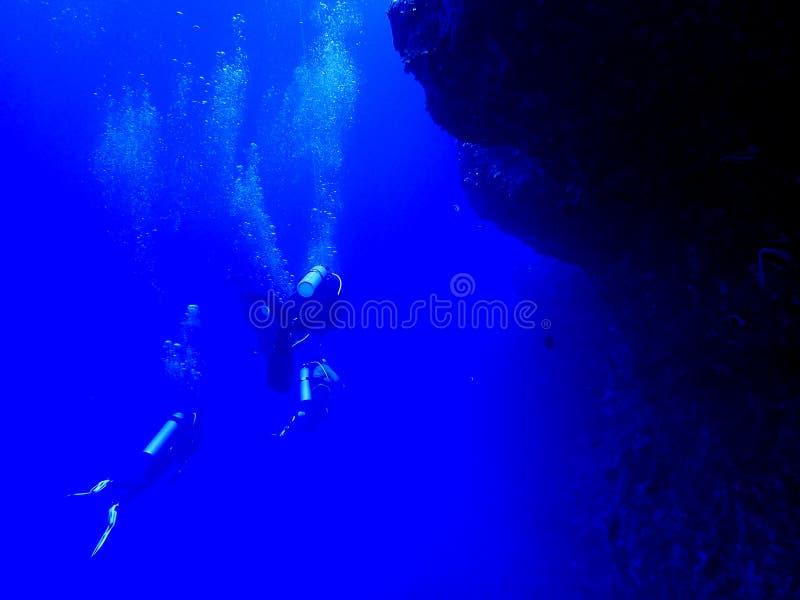 Plongeurs le long de mur dans le bleu profond avec des bulles photographie stock