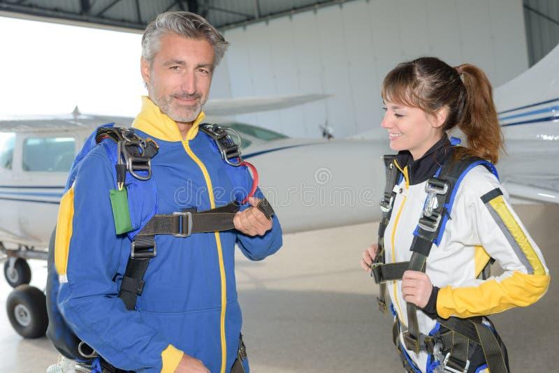 Plongeurs masculins et féminins de ciel préparant leurs harnais images stock