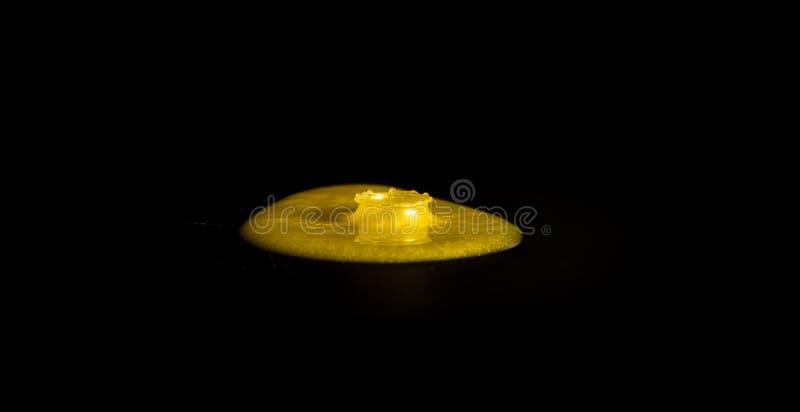 Plons in een gele verf stock fotografie