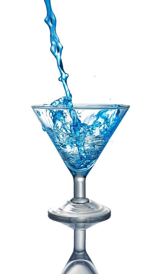 Plons in glas van een blauwe alcoholische cocktaildrank stock foto's