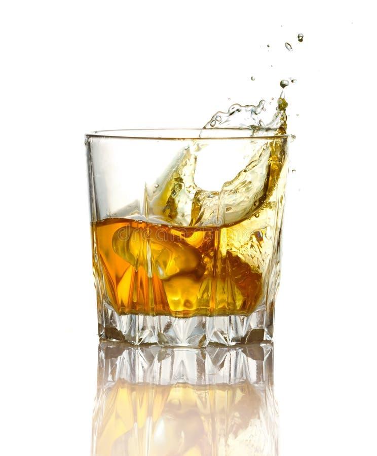 Plons in glas whisky en ijs   stock foto