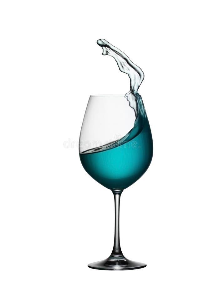 Plons van blauwe drank in glas op wit geïsoleerde achtergrond Het bespatten van blauw water is als een overzeese golf in een glas royalty-vrije stock afbeelding
