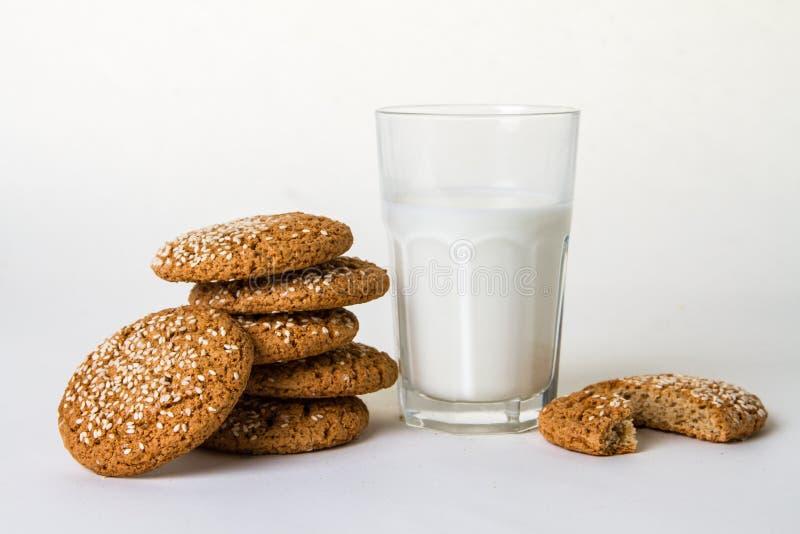 Plons van melk met koekjes op wit stock fotografie