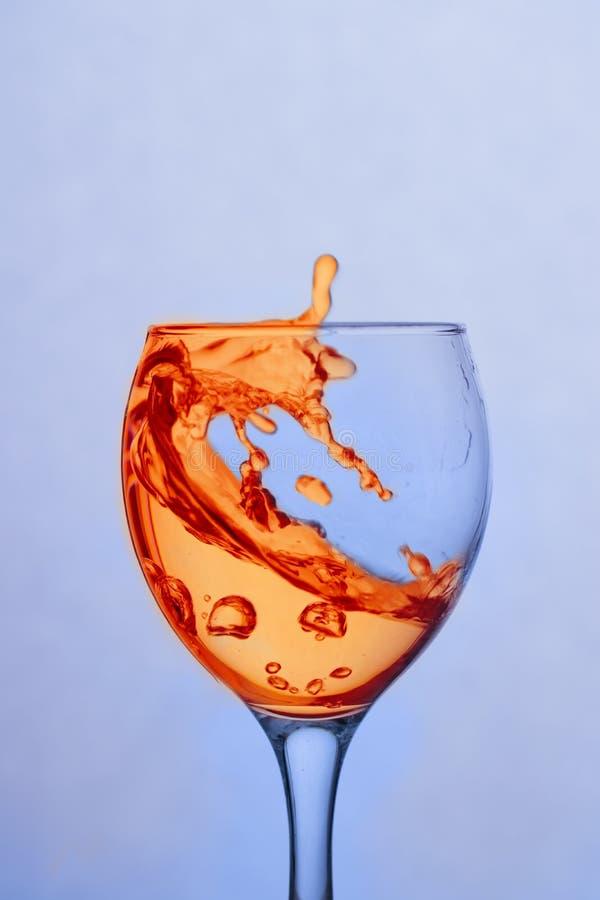 Plons van oranje vloeistof in een glas royalty-vrije stock afbeeldingen