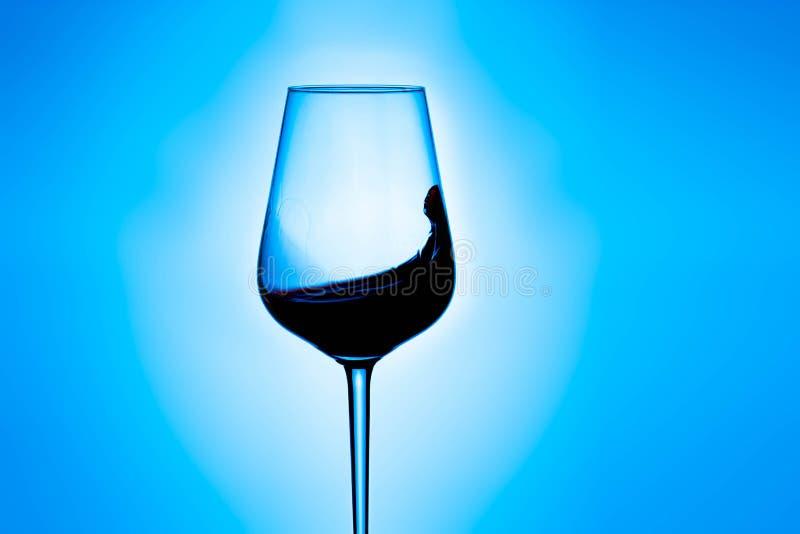 Plons van rode wijn in een glas stock fotografie