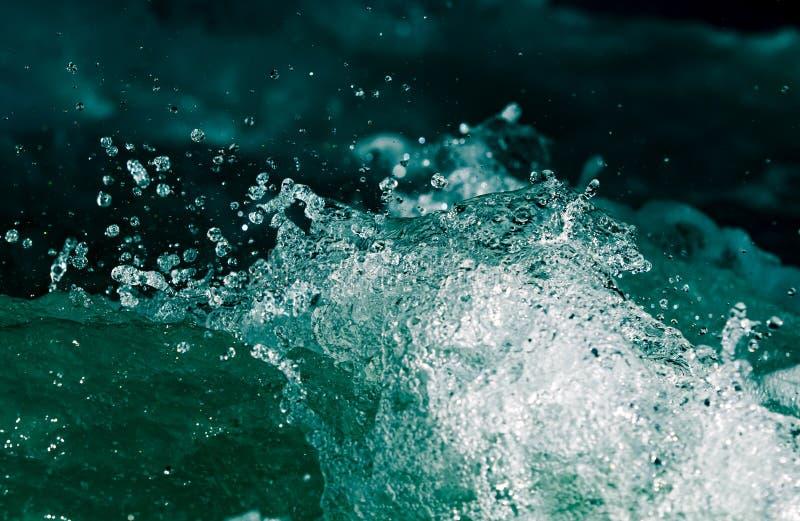 Plons van stormachtig water in de oceaan op een zwarte achtergrond royalty-vrije stock afbeeldingen
