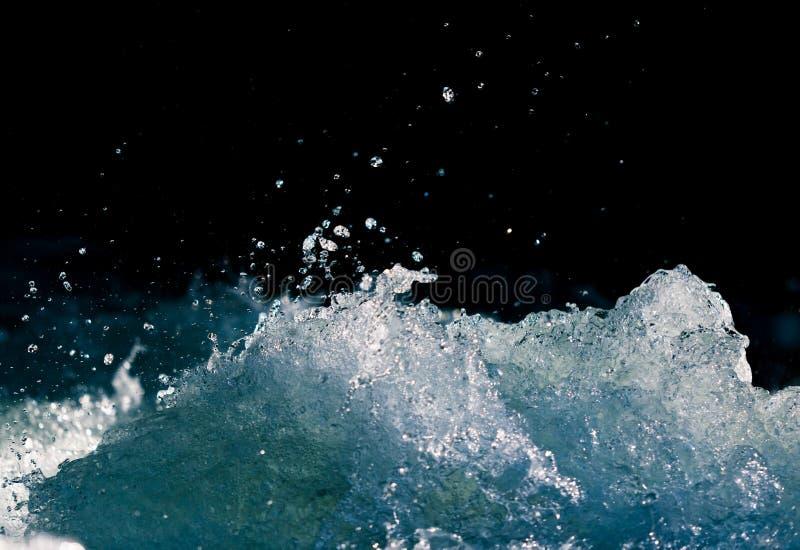 Plons van stormachtig water in de oceaan op een zwarte achtergrond stock foto