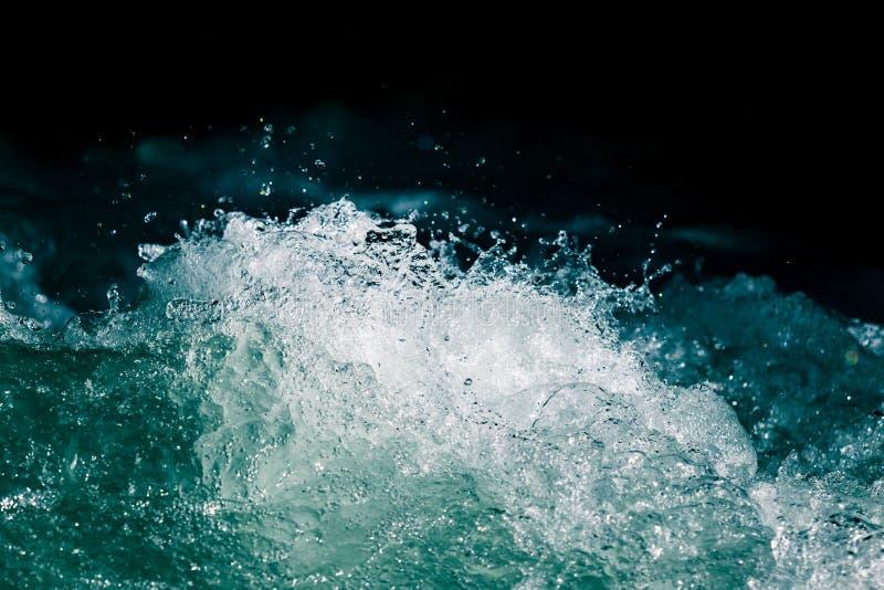 Plons van stormachtig water in de oceaan op een zwarte achtergrond stock fotografie