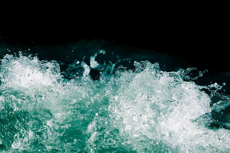 Plons van stormachtig water in de oceaan op een zwarte achtergrond stock foto's