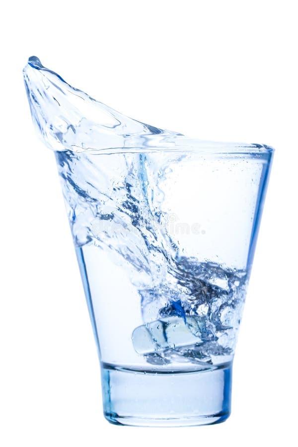 Plons van water in een elegant glas met geïsoleerd ijs stock fotografie